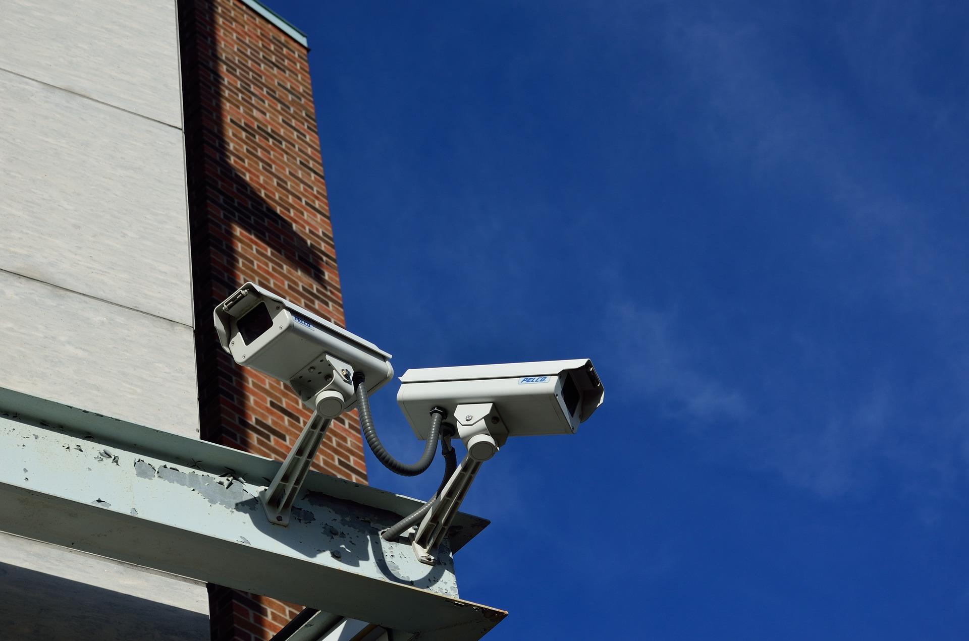 2 caméras de' vidéosurveillance en extérieur sous un ciel bleu