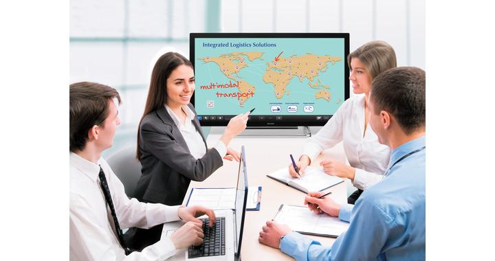 une femme avec 3 hommes en réunion de travail, présentant des graphiques sur un écran interactif