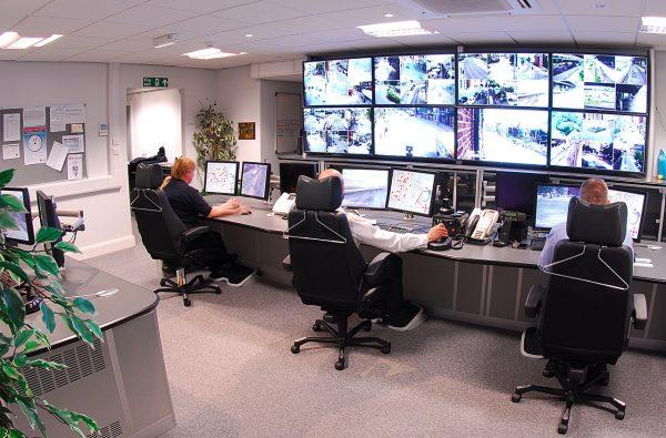 centre de vidéosurveillance avec 3 hommes observant des écrans